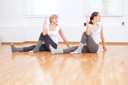 Group of sport women in the gym centre doing stretching fitness exercise. Yoga Stock Photo - 12535377
