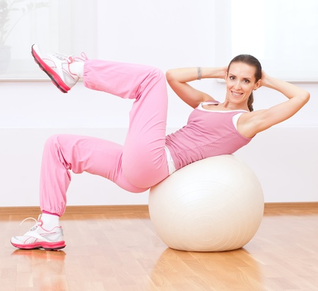 wellness center: Beautiful sport woman doing stretching fitness exercise on ball at sport gym