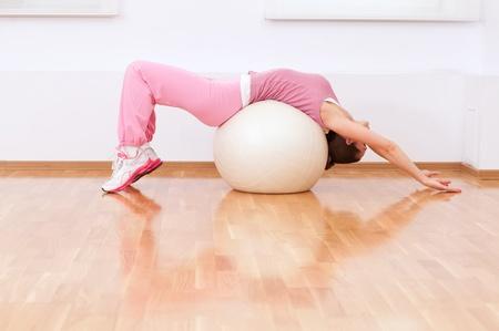 Mooie sport vrouw doet stretching fitness oefeningen op de bal in sport sportschool