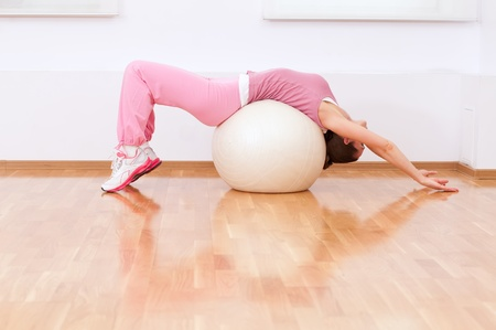 Mujer de hermoso deporte haciendo ejercicios de estiramiento en la pelota de fitness en el gimnasio de deporte