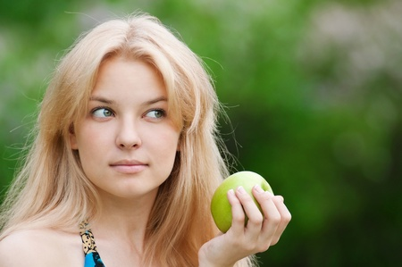 Portrait of a young beautiful woman with green apple at park photo