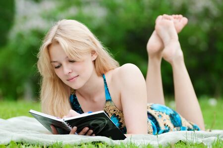Beautiful young woman read book, at green summer park photo