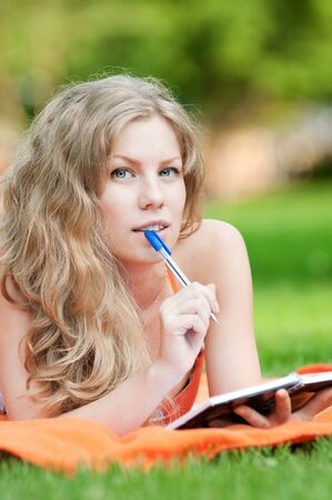 Beautiful young woman study at green summer park photo