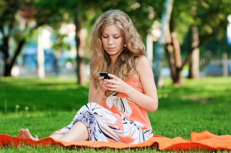 Young happy woman texting on mobile phone. SMS Stock Photo