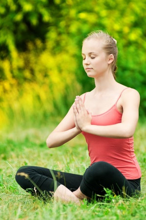 Beautiful young woman doing stretching exercise on green grass at park. Yoga Stock Photo - 12535516