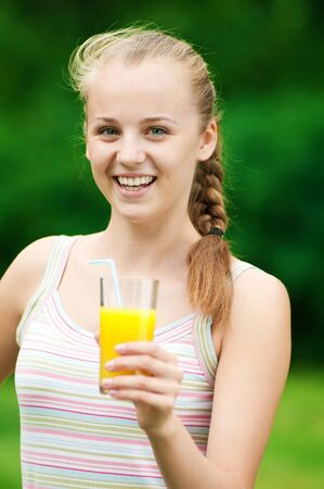 Young woman drinking orange juice after outdoor fitness exercise photo