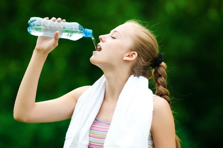 Young woman drinking water after fitness exercise photo