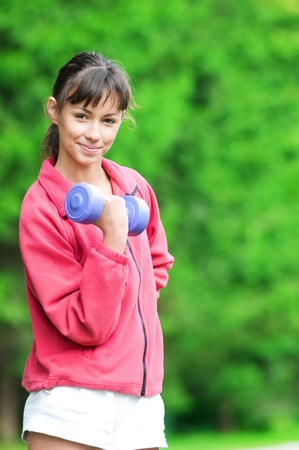 Beautiful teenage girl doing dumbbell exercise on green grass at park photo