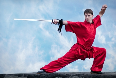aikado: Shaolin warriors wushoo man in red with sword practice martial art outdoor. Kung fu