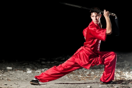 Shaolin warriors wushoo man in red practice martial art outdoor. Kung fu Stock Photo - 12535631