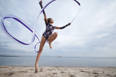young professional gymnast woman dance with ribbon - outdoor sand beach photo