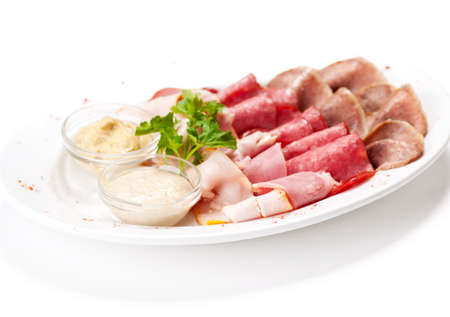Meat delicatessen plate arranged with parsley and two sauce. Isolated on white Stock Photo - 12872319