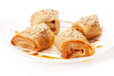 Rolled pancakes with caramel mousse and nuts. On white Stock Photo - 12872294