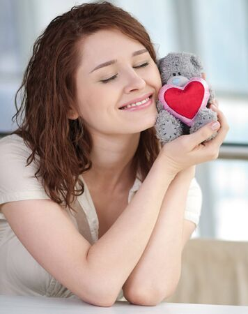 Beautiful young woman with a toy bear indoor. Love Stock Photo - 12872340