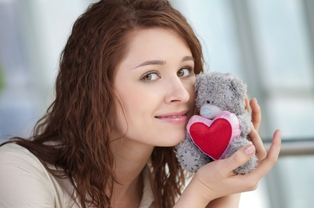 Beautiful young woman with a toy bear indoor. Love