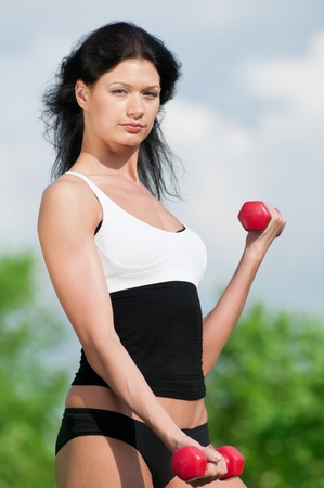 Young woman lifting small weights in the park photo