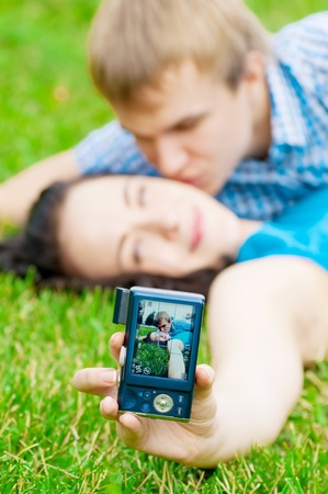 Young emotional happy teenage couple taking picture on grass in city park Stock Photo - 12872156