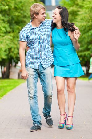 Portrait of a beautiful young happy smiling couple - walking at green park outdoor photo