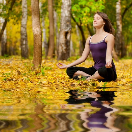 Young woman doing yoga exercises in the autumn city park lake. Fall with mirror in water photo