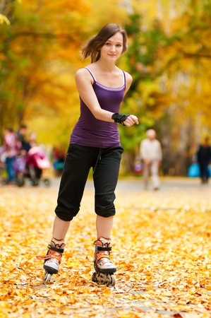 happy young woman on roller skates in the autumn park  Stock Photo - 12872122