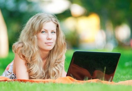 Young woman with laptop on green grass at park photo
