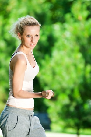 Beautiful young woman doing dumbbell exercise on green grass at park Stock Photo - 12872045
