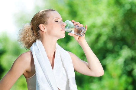 water drink: Young woman drinking water after fitness exercise