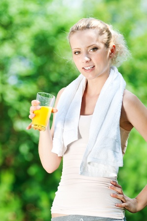 Young woman drinking orange juice after fitness exercise Stock Photo - 12871968