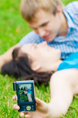 Young emotional happy teenage couple taking picture on grass in city park Stock Photo - 13303865