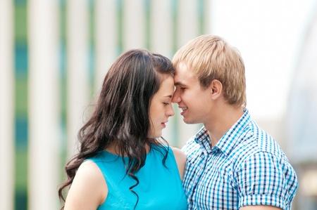 young couple kiss: Retrato de una hermosa joven pareja sonriente feliz - caminar en verde parque al aire libre