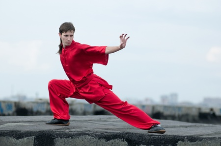 aikado: Shaolin warriors wushoo man in red practice martial art outdoor. Kung fu