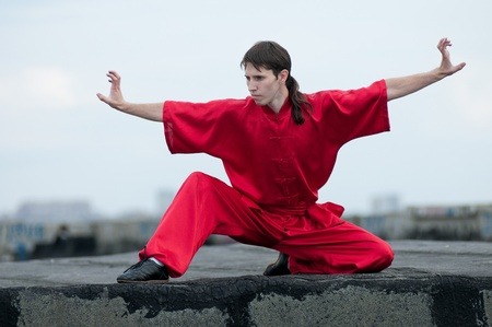 Shaolin warriors wushoo man in red practice martial art outdoor. Kung fu Stock Photo - 13303986
