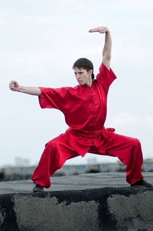 Shaolin warriors wushoo man in red practice martial art outdoor. Kung fu photo