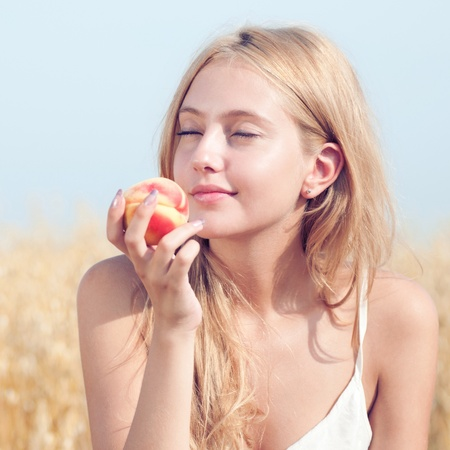 Young happy woman in wheat field with peach. Summer picnic Stock Photo