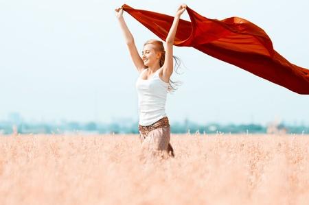 ファブリックと麦畑の若い幸せな女性。夏のピクニック 写真素材