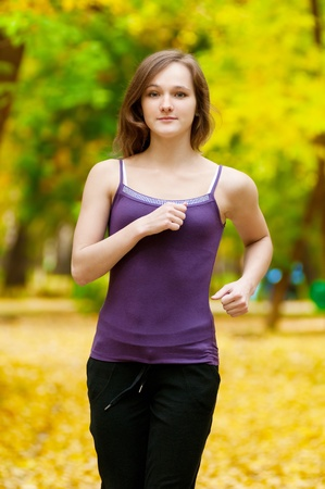 Young woman running outdoors on a lovely sunny winter (fall) day Stock Photo - 13303693