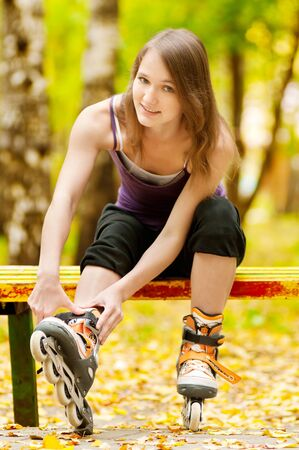 rollerblading: happy young woman on roller skates in the autumn park