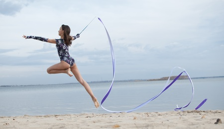 young professional gymnast woman dance with ribbon - outdoor sand beach Stock Photo - 13304067