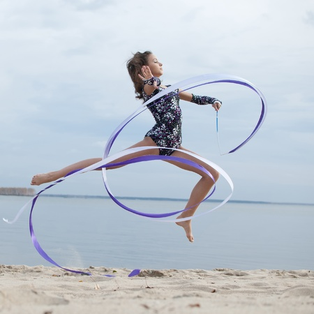 gimnasia ritmica: joven gimnasta profesional de baile la mujer con la cinta - Playa de arena al aire libre