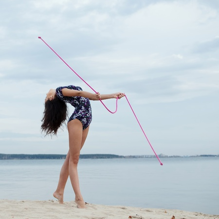 young professional gymnast woman dance with skipping rope - outdoor sand beach photo