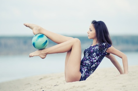young professional gymnast woman dance with ball - outdoor sand beach photo