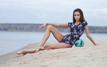 acrobatics: young professional gymnast woman dance with ball - outdoor sand beach