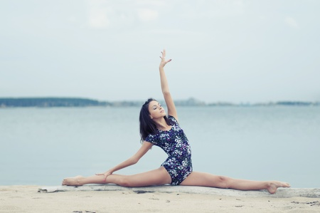 young professional gymnast woman dance - outdoor sand beach photo