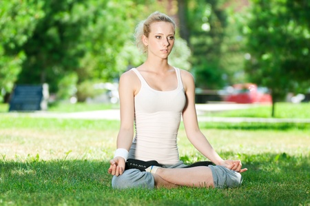 Beautiful young woman doing stretching exercise on green grass at park. Yoga Stock Photo - 13321514