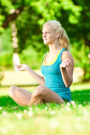 Beautiful young woman doing stretching exercise on green grass at park. Yoga photo
