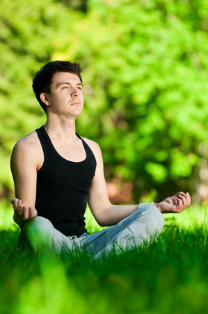 A young man doing yoga in the green park photo