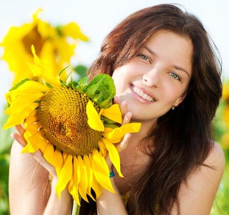 salud sexual: Joven mujer hermosa en un campo de girasol. Verano de picnic Foto de archivo