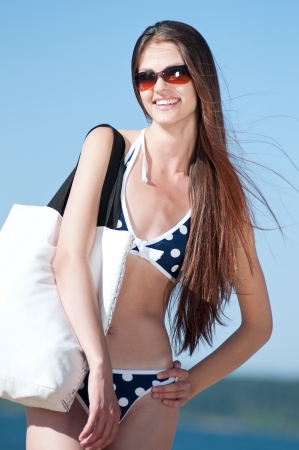 Happy woman with white bag at the beach enjoying her summer holidays Stock Photo - 13622207