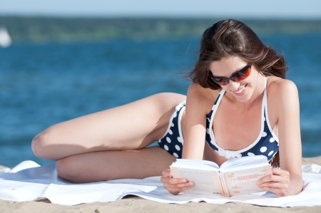 Close up of a beautiful young woman reading book on beach Stock Photo - 13622140