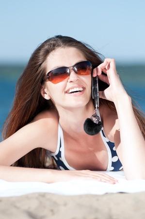 Joven mujer sonriente hablando por tel�fono en una playa Foto de archivo - 13622143